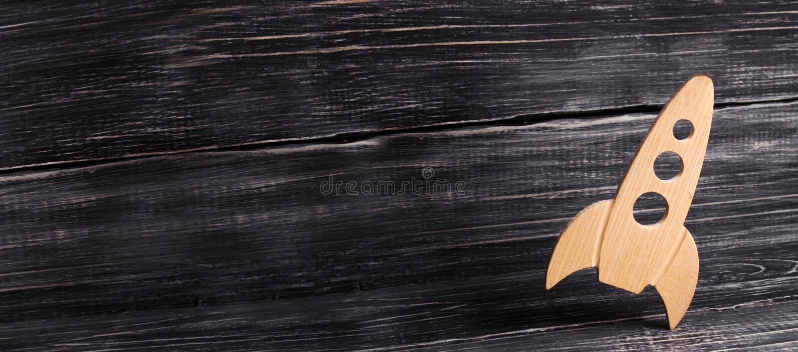 Wooden space rocket in retro style is on a dark wooden background. The space industry, the development of technology royalty free stock photo