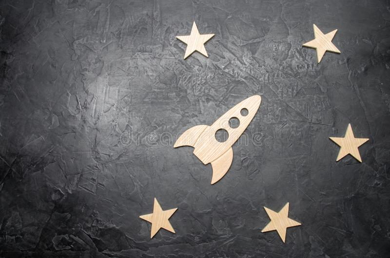 Wooden space rocket and stars on a dark background. The concept of space travels, the study of planets and stars. Education royalty free stock images