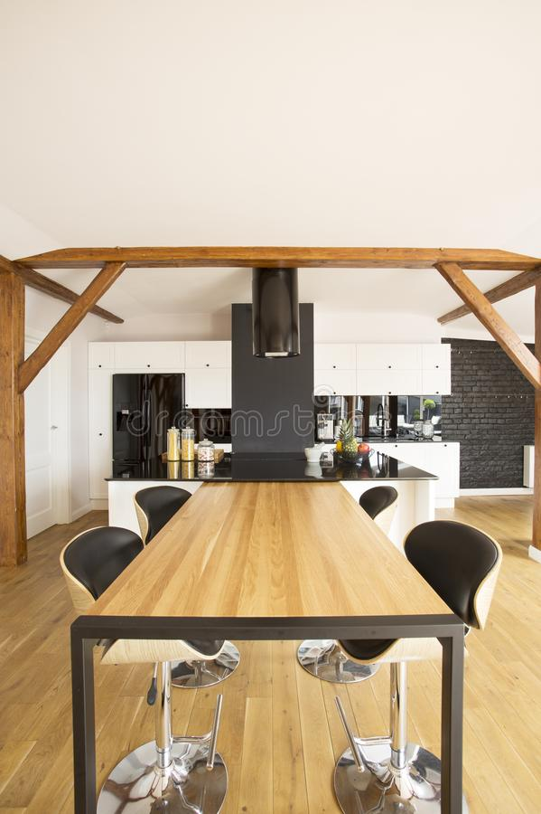 Wooden spacious kitchen interior. Bar stools at wooden table in spacious kitchen interior with black countertop and white cabinets royalty free stock images