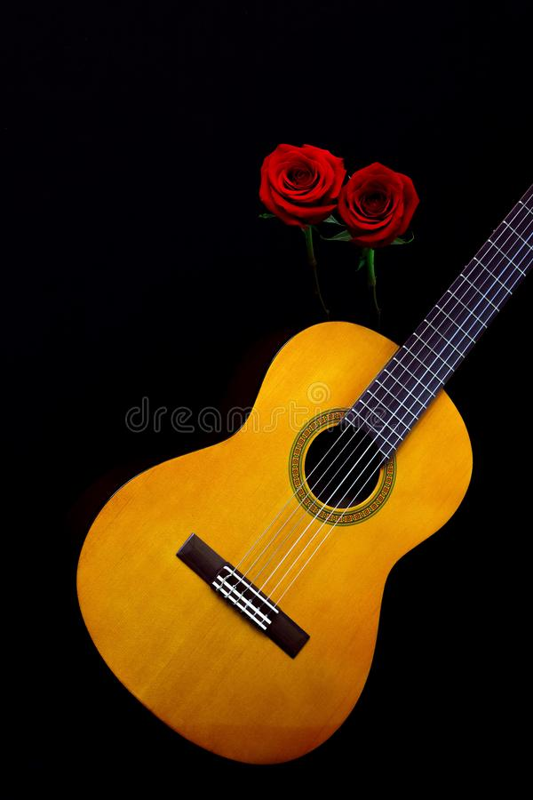 Traditional spanish guitar with a pair of valentine red roses against black background. Wooden spanish guitar with lovely valentine red roses against black stock photo