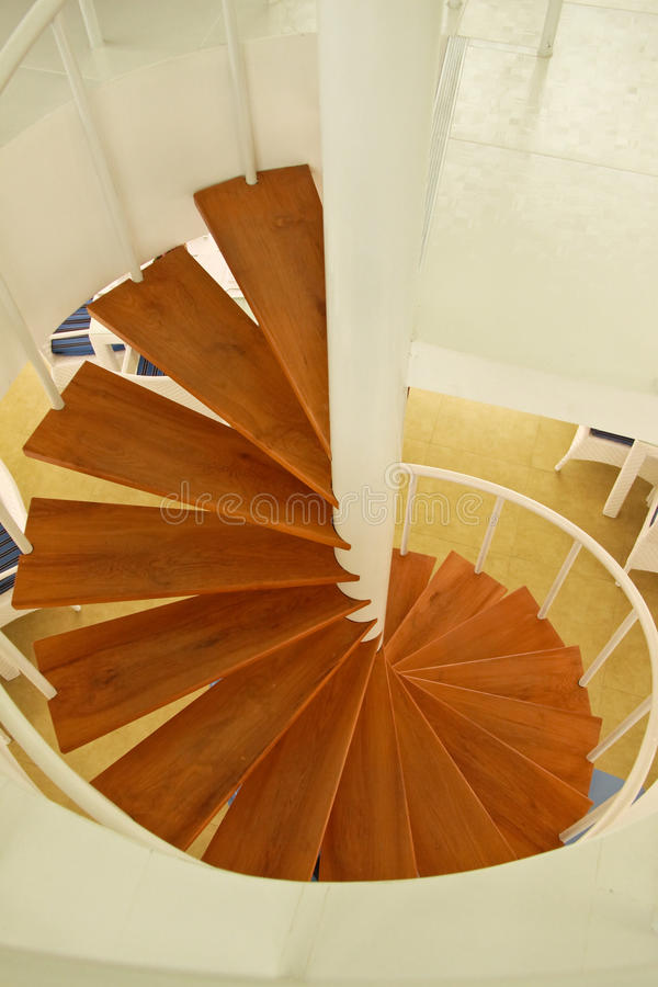 Wooden spiral stairway. And white painted-metal structure stock photo