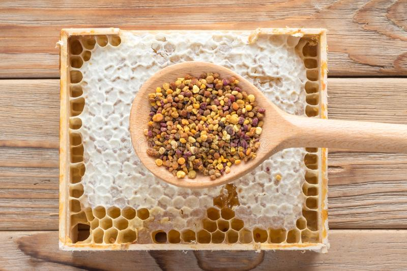 Top view of the wooden spoon of bee pollen with honeycombs on wooden background royalty free stock photo