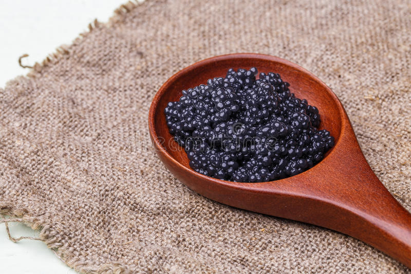 Wooden spoon with black caviar royalty free stock photo