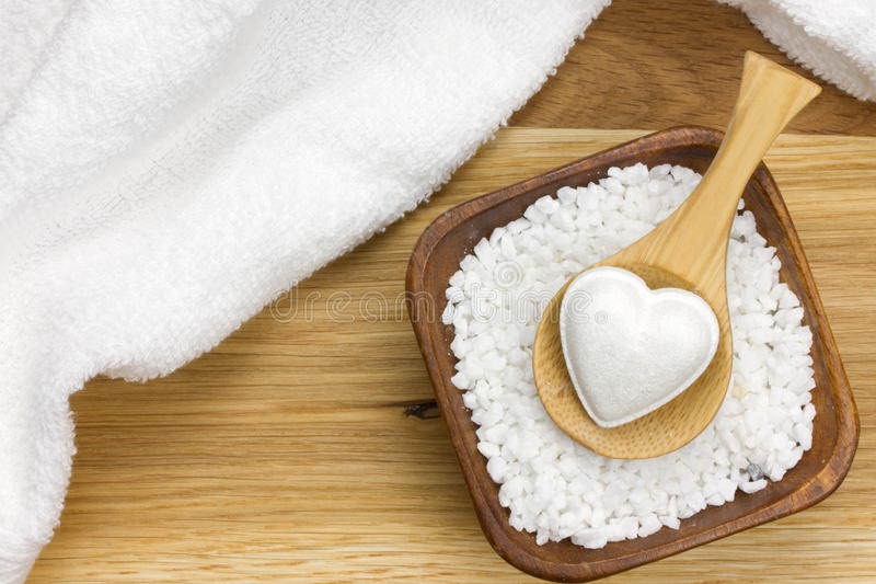 Wooden spoon in bowl filled with bath salt and towel. Wooden spoon with bath fizzer in heart shape on bowl filled with bath salt and white towel next to it royalty free stock photo