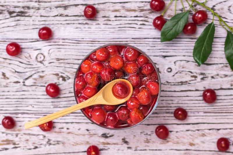 Wooden spoon in a Cup of cherry jam on a wooden table. Homemade jam from the fresh harvest of cherry berries. Flat lay. Wooden spoon in a Cup of cherry jam on a stock photos