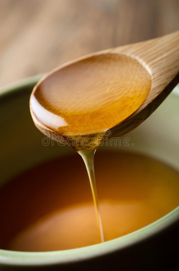 Honey Dripping from Wooden Spoon into Bowl royalty free stock photos