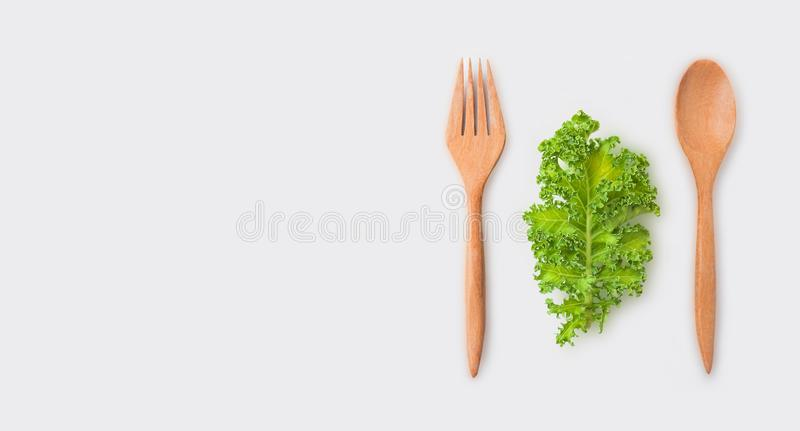 Wooden spoon and fork with organic green leaves isolated on white or gray background. Healthcare and healthy food design concept. royalty free stock photos