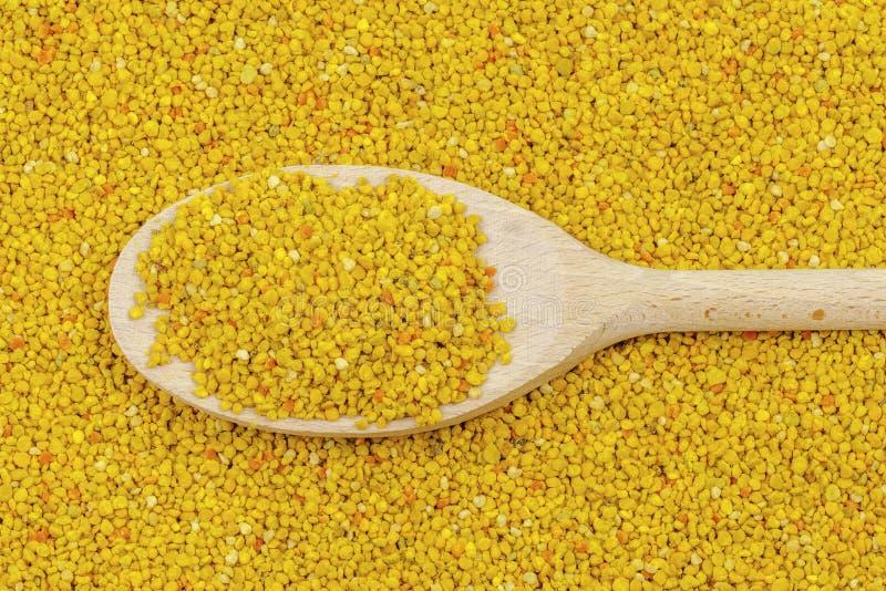 Wooden spoon on fresh bee pollen. Backgrounds stock photo
