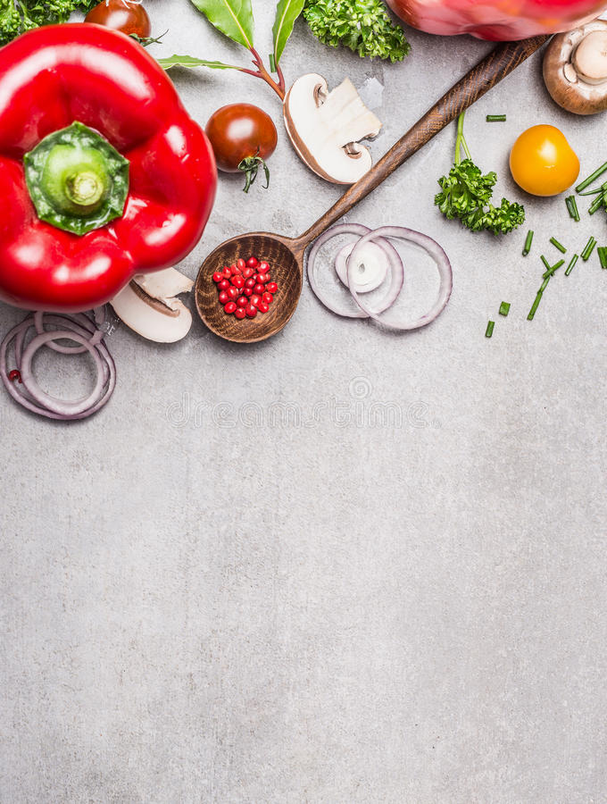 Wooden Spoon and Healthy vegetables and seasoning ingredients for fresh tasty cooking on gray stone background, top view composin. G. Healthy eating and diet royalty free stock photography
