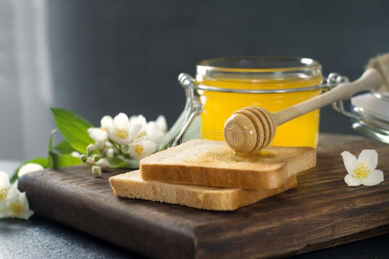 Wooden spoon with honey is lying on a piece of bread near a glass jar of honey stock images