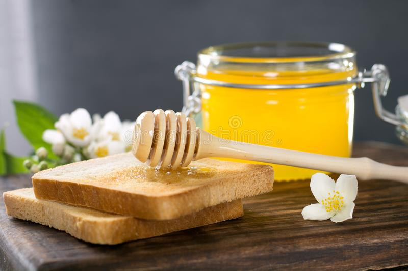 Wooden spoon with honey is lying on a piece of bread near a glass jar of honey stock photos