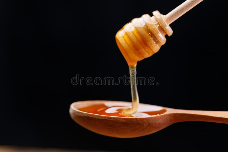 A wooden spoon and honey pouring from it. Close-up royalty free stock photos
