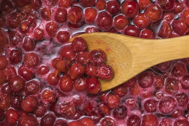 Wooden spoon in the jam from the ripe cherries. Cooking homemade jam royalty free stock photos
