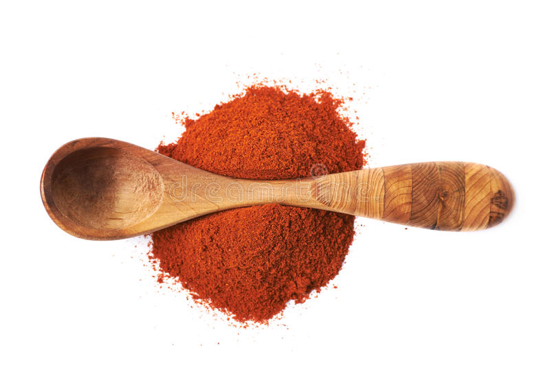 Wooden spoon over the pile of paprika. Isolated over the white background stock photography