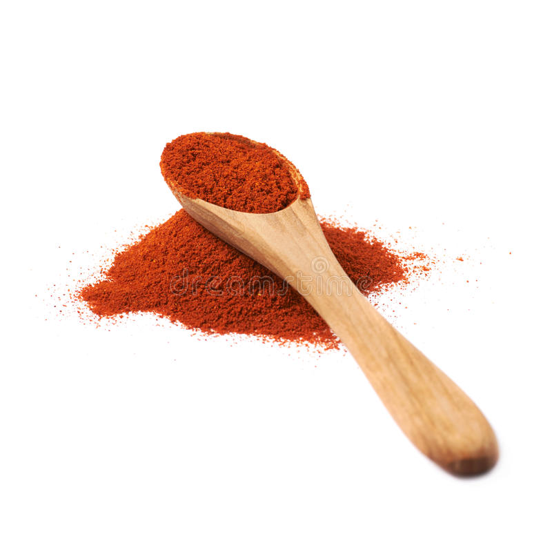 Wooden spoon over the pile of paprika. Isolated over the white background royalty free stock images