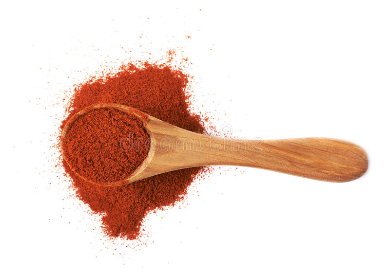 Wooden spoon over the pile of paprika. Isolated over the white background royalty free stock image