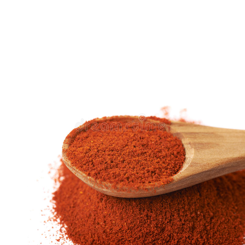 Wooden spoon over the pile of paprika. Isolated over the white background, close-up crop fragment royalty free stock photography