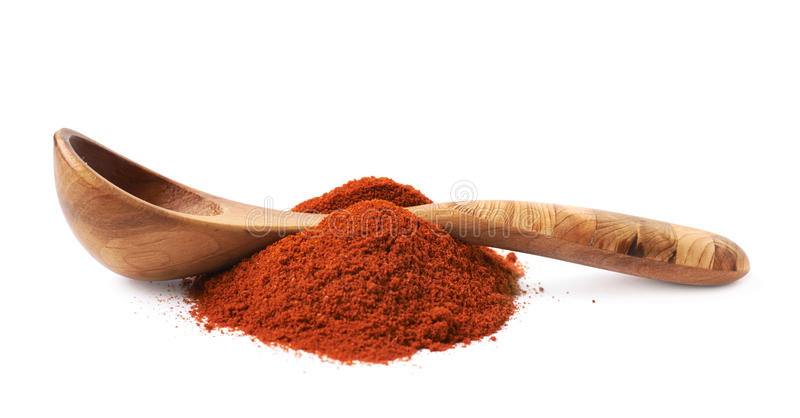 Wooden spoon over the pile of paprika. Over the white background stock image
