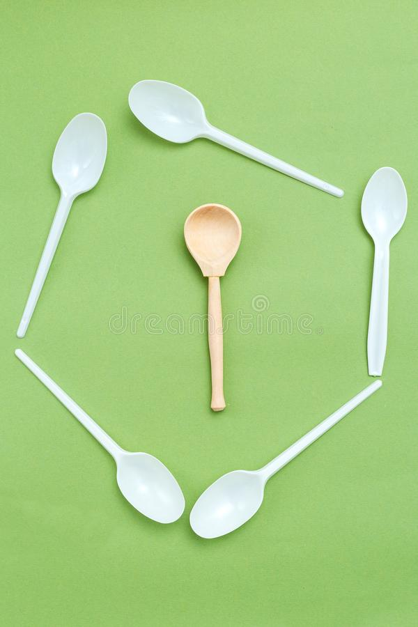 Wooden spoon with plastic alternatives on green background. Vertical. Organic concept. Wooden spoon with plastic alternatives on green background. Vertical photo royalty free stock photos