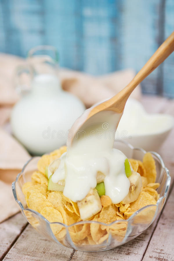 Wooden spoon pouring yogurt on corn flakes with green apple and stock photos