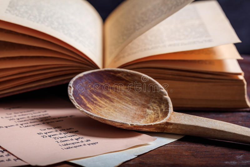 Wooden spoon and a vintage book. Cookbook concept. Wooden ladle and a cooking recipe royalty free stock images