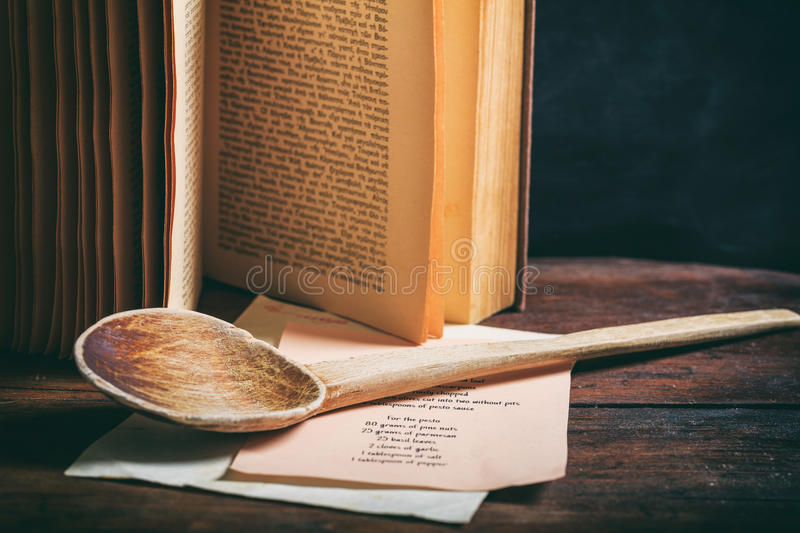 Wooden spoon and a vintage book. Cookbook concept. Wooden ladle and a cooking recipe royalty free stock image