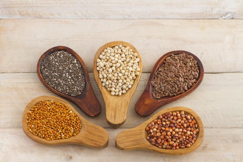 Wooden spoons with assorted grains of super foods, gluten free stock images