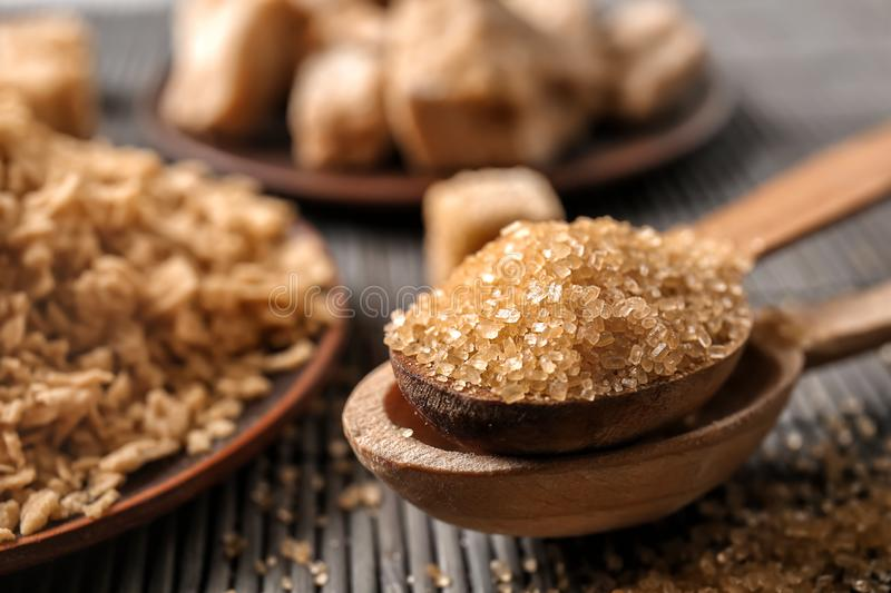 Wooden spoons with brown sugar on table, closeup stock photos