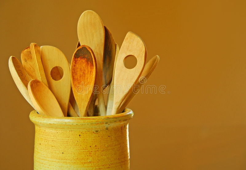 Wooden Spoons in Crock. Warmly lit pottery crock with worn wooden spoons inside stock photography