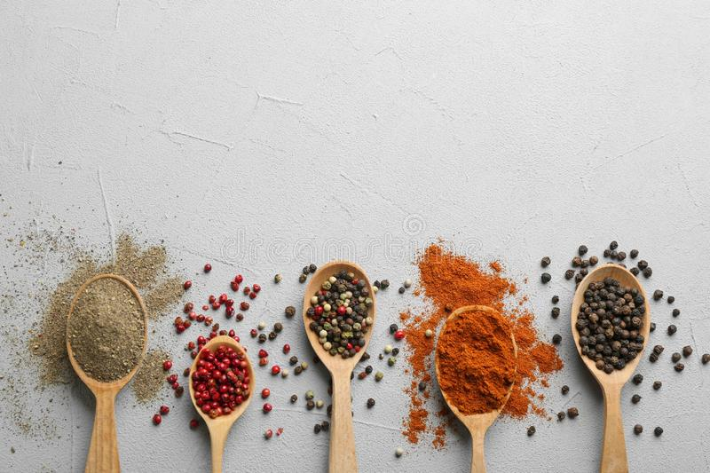 Wooden spoons with different ground pepper and corns on grey table, flat lay. stock photography
