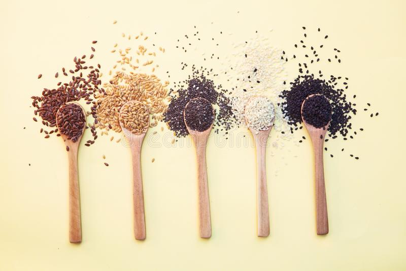 Wooden spoons with different seeds isolated on yellow background royalty free stock photos
