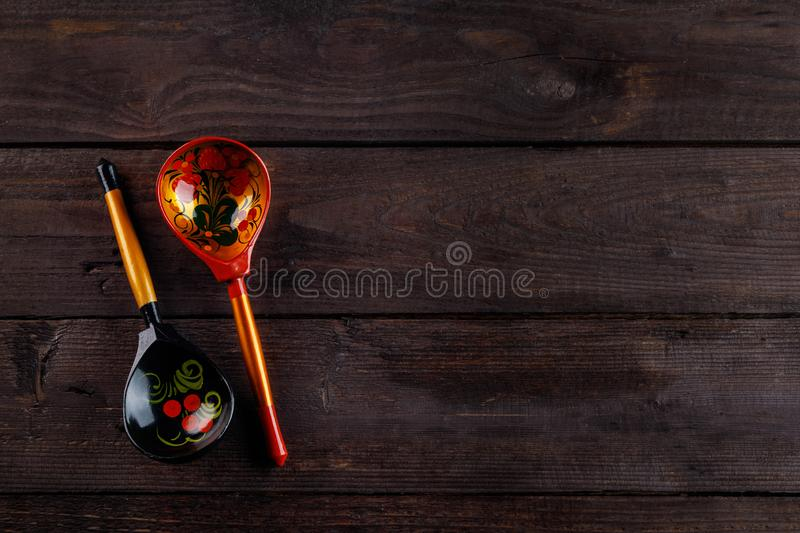 Wooden spoons with floral ornament in traditional folk Russian Khokhloma style on a wooden background. Two spoons with a stock photos