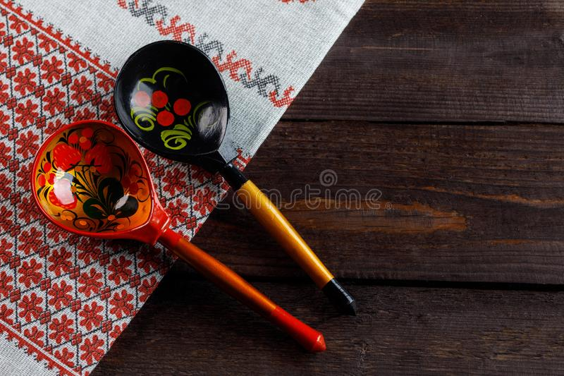 Wooden spoons with floral ornament in traditional folk Russian Khokhloma style on wooden table with a tablecloth with a royalty free stock photo