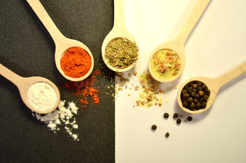 Pepper, salt, chilli and basil in wooden spoon stock photo