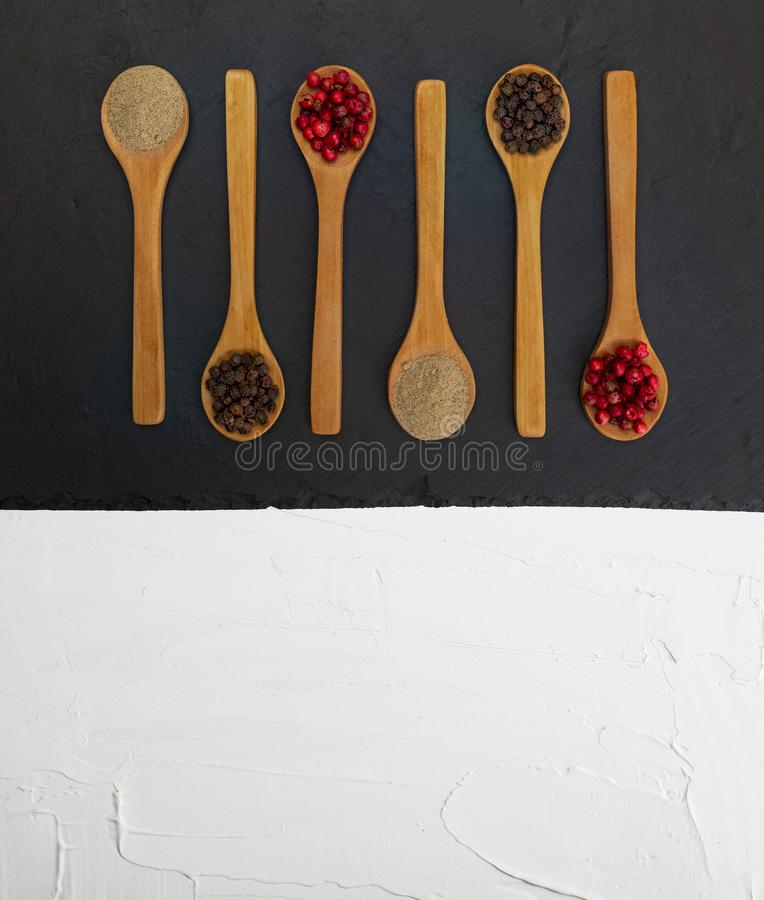 Wooden spoons with spices on black and white textured background. stock photos