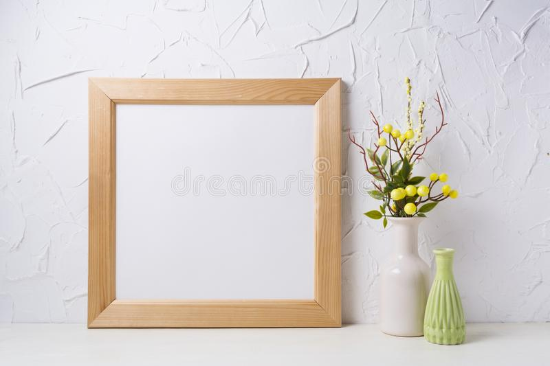 Wooden square frame mockup with yellow decoration stock photography