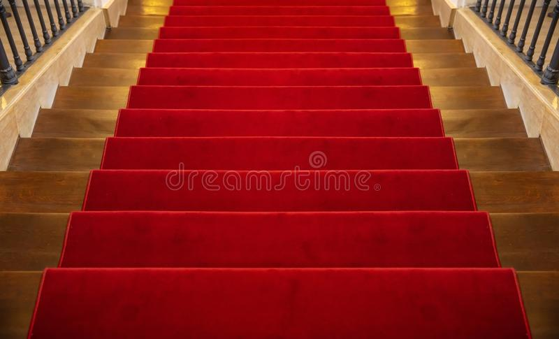 Wooden staircase covered with red carpet background royalty free stock photography