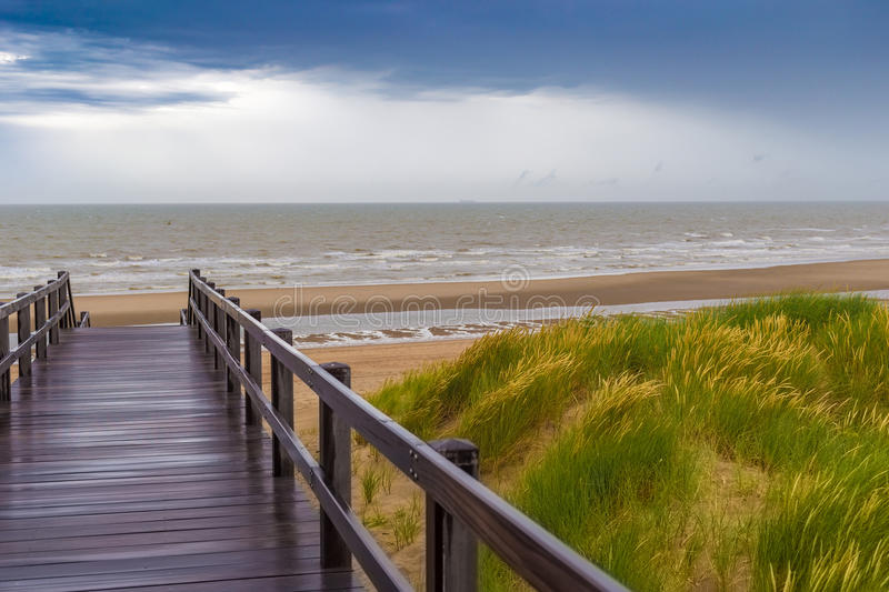 Wooden staircase leading into stormy sky and sea at De Haan, Belgium.  stock photo
