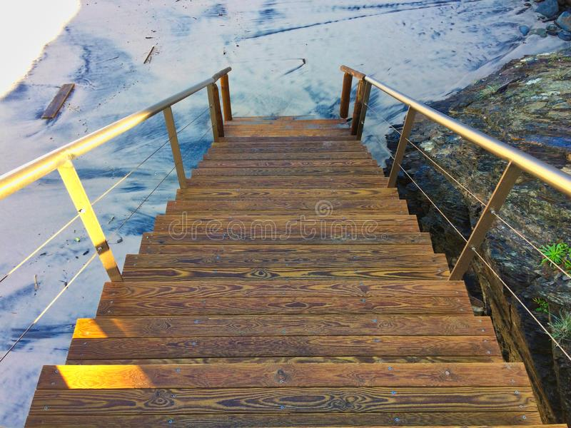 Wooden staircase leading to the sandy beach, wood patterns. Trash on the sandy beach stock images