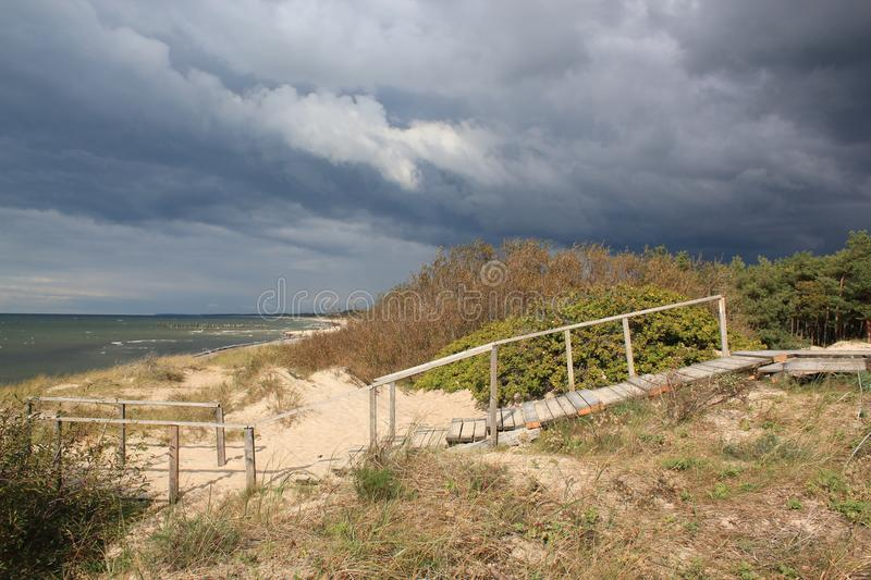 Wooden Stairs In Dunes And Forest Near The Baltic Sea Sand Beach / Scary frightening storm clouds royalty free stock images