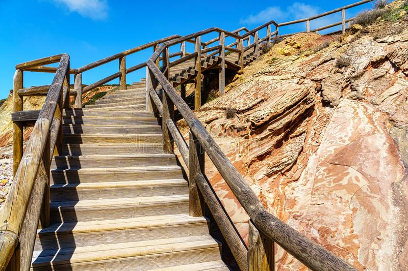 Wooden stairs with handrails leading up a rock stock photo