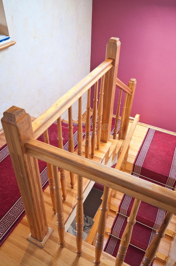 Wooden stairs in a home with red carpets royalty free stock image