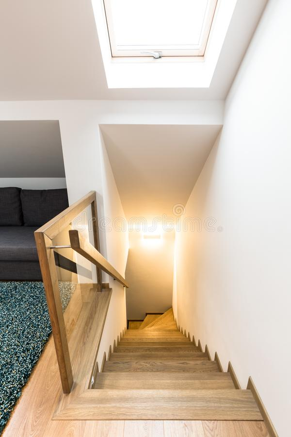 Wooden stairs of house interior. High angle of wooden stairs of house white hall interior with lights and window royalty free stock photography