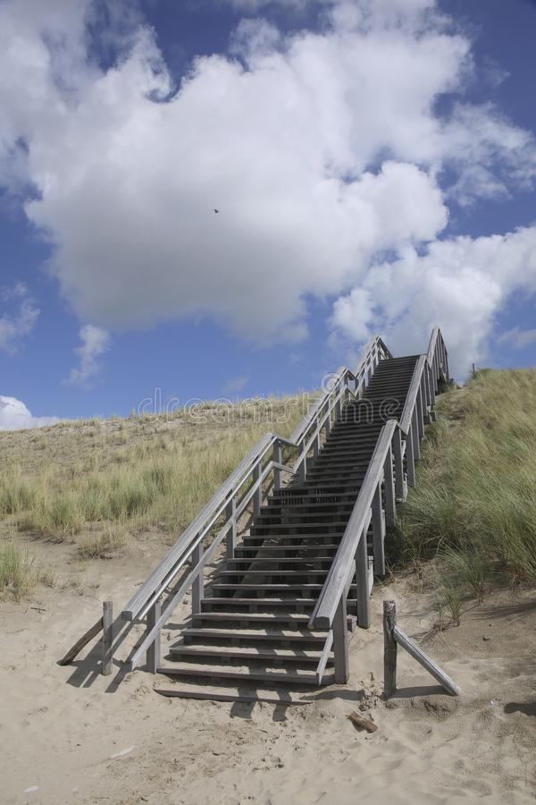 Wooden stairway in the dunes, Petten, Netherlands. A wooden stairway in the dunes in Petten, The Netherlands. This stairway is the access to and the exit from royalty free stock photography