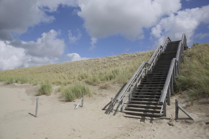 Wooden stairway in the dunes, Petten, Netherlands. A wooden stairway in the dunes in Petten, The Netherlands. This stairway is the access to and the exit from stock photography