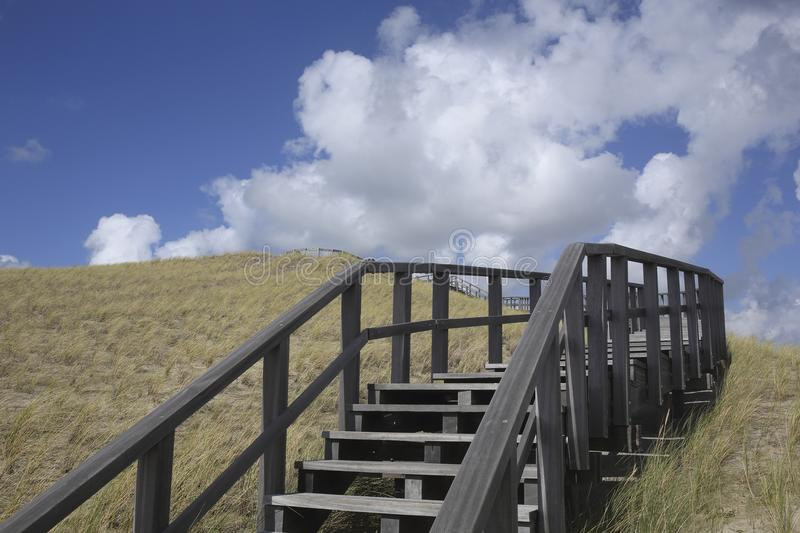 Wooden stairway in the dunes, Petten, Netherlands. A wooden stairway in the dunes in Petten, The Netherlands. This stairway leads to a viewing point from which stock photos