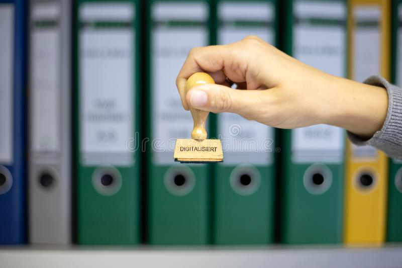 A wooden stamp with the german word. `digitalisiert ` which means `digitized ` is held in front of a bookshelf with folders, depth of field royalty free stock image
