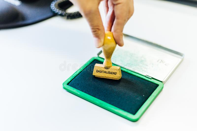 A wooden stamp with the german word. `digitalisiert ` which means `digitized ` is pressed on a green inkpad royalty free stock photos