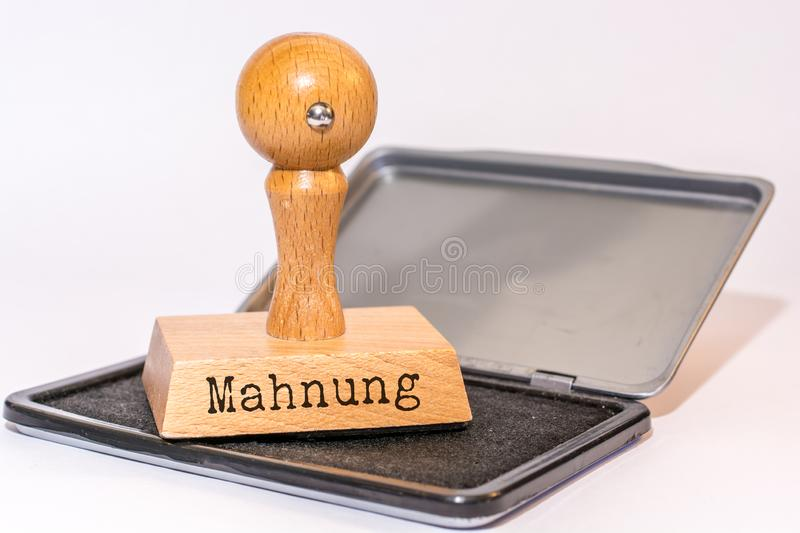 Ink pad and stamp with the German word `reminder`. Wooden stamp with the inscription in German for reminder on ink pad stock photos