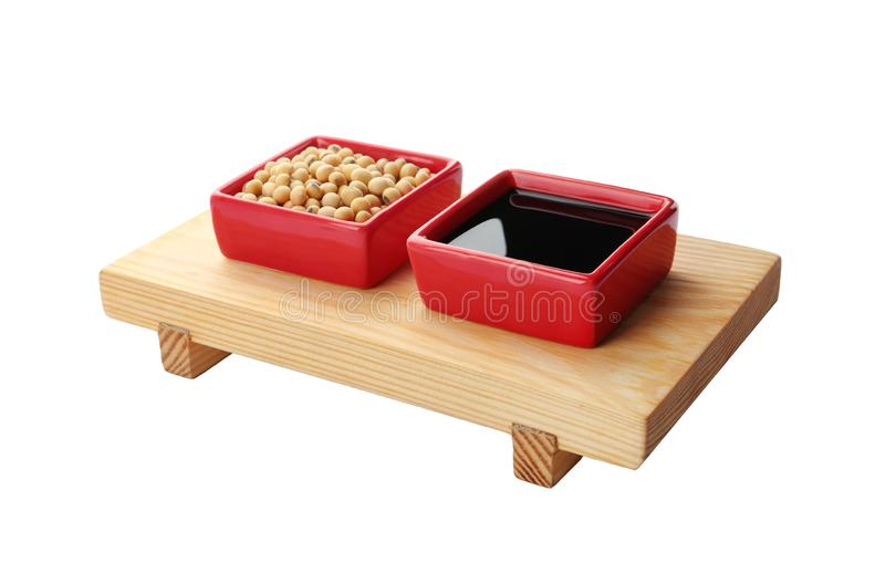 Wooden stand with dishes of soy sauce and beans on white royalty free stock photos
